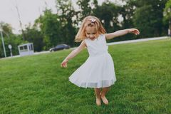 Pretty little cute child baby girl in light dress circling around and have fun on green grass lawn in park. Mother. Little kid daughter. Mother`s Day, love stock photos
