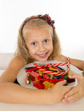 Pretty little female child eating dish full of candy caramel and sweet food Stock Images