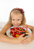 Pretty little female child eating dish full of candy caramel and sweet food in sugar abuse and unhealthy diet Royalty Free Stock Image