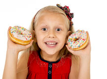 Pretty little female child holding two sugar donuts smiling happy  Royalty Free Stock Photography