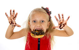 Pretty little female child with long blond hair and blue eyes wearing red dress bitting donut mouth showing dirty hands. Pretty little female child with long royalty free stock photo