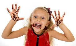 Pretty little female child with long blond hair and blue eyes wearing red dress showing dirty hands with stains of chocolate syrup. Pretty little female child royalty free stock photography