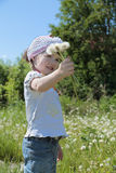 Pretty little gilr in hat holds dandelions and smiles. At summer. Focus on hand Royalty Free Stock Photo