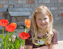 Pretty Little Girl. Little Girl Sitting in Front of Home with Tulips Stock Photos
