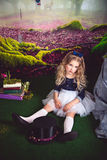 Pretty little girl as Alice in Wonderland and magician hat. Little sitting on the floor girl in a beautiful dress in the image of Alice in Wonderland and royalty free stock photos