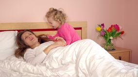 Pretty little girl awake her sleeping mom in morning stock footage