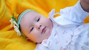 A pretty little girl, baby, lies on a yellow plaid, on the grass. On her head is a bandage with chamomile. stock footage