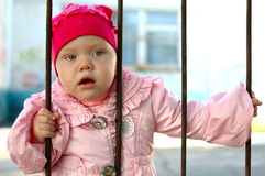 Pretty little girl behind old railing. Curious pretty little girl behind old railing (grille royalty free stock photo