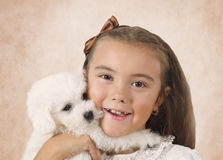 Pretty little girl with Bichon Frise puppy. Portrait of pretty little girl with Bichon Frise puppy on a beige background Royalty Free Stock Image