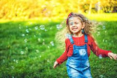 Pretty little girl blowing bubbles in the park. Pretty little girl blowing bubbles in the park stock photography