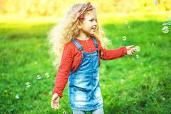Pretty little girl blowing bubbles in the park. Pretty little girl blowing bubbles in the park stock photos