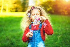 Pretty little girl blowing bubbles in the park. Pretty little girl blowing bubbles in the park royalty free stock photo