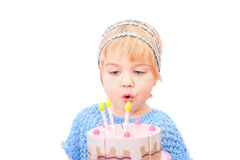 Pretty little girl blowing on candles in the cake Royalty Free Stock Images