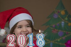 New Year 2018 concept. Pretty little girl in a Santa Claus hat blowing out candles - closeup shot Royalty Free Stock Image
