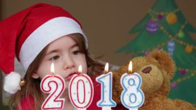 Pretty little girl in a Santa Claus hat blowing out candles. Little girl holding a Christmas teddy bear stock video