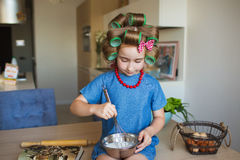 Pretty little girl in blue dress and with curlers whips up a cream on a kitchen Royalty Free Stock Images