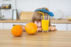 Pretty little girl in blue dress sits behind two oranges at the table Royalty Free Stock Images
