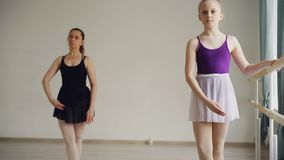 Pretty little girl in bodysuit and tutu is having individual ballet practice learning movements and positions with. Pretty little girl in bodysuit, pointe shoes stock video footage
