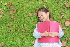 Pretty little girl with book lying on green grass with dried leaves in the summer garden.  royalty free stock image