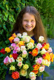 Pretty little girl with bouquet of flowers roses. Royalty Free Stock Photo