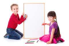 Pretty little girl and boy drawing on board. Pretty little girl and boy drawing on blank board Royalty Free Stock Photos