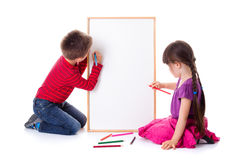 Pretty little girl and boy drawing on board. Pretty little girl and boy drawing on blank board Royalty Free Stock Image