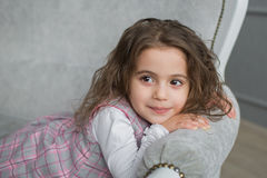 Pretty little girl with brown hair sits on a grey sofa and looks away Stock Image