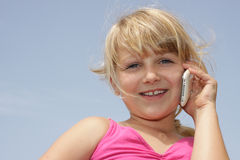 Pretty little girl chatting on her cellphone. Horizontal photo of cute young girl talking on her mobile phone, Positive feeling. Space for text Royalty Free Stock Images