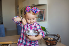 Pretty little girl in checkered shirt whips up a cream on a kitchen Royalty Free Stock Images