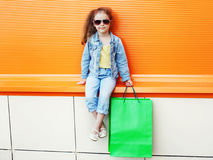 Pretty little girl child wearing a jeans clothes with shopping bags Stock Photography