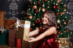 Pretty little girl with a Christmas present Stock Photos
