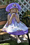 Pretty little girl in colorful dress and hat Stock Photo