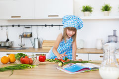Pretty little girl in cook clothes reads a recipe book on a kitchen Stock Images