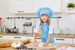 Pretty little girl in a cook clothes sculpts a circle of dough on a table and smiles. Pretty little girl in a cook clothes sculpts a circle of dough on table and Royalty Free Stock Photo