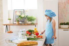Pretty little girl in cook clothes thinks on a kitchen. Pretty little girl in cook clothes thinks on kitchen Royalty Free Stock Photo