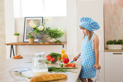Pretty little girl in cook clothes thinks on a kitchen. Pretty little girl in cook clothes thinks on kitchen Stock Photos