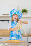 Pretty little girl in a cook plays with a dough in a hands and smiles Royalty Free Stock Photo