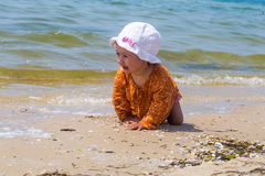 Pretty little girl crawling on the beach, the joyful child, emotions Stock Photography