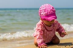 Pretty little girl crawling on the beach, the joyful child, emotions Royalty Free Stock Photos