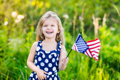 Pretty little girl with  curly blond hair holding american flag Royalty Free Stock Photos