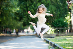 Pretty little girl with curly blonde hair jumping on street Royalty Free Stock Photos