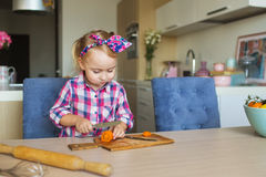 Pretty little girl cuts and eats a vegetable on a kitchen Stock Photo