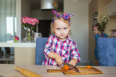 Pretty little girl cuts a vegetable on a board on a kitchen Royalty Free Stock Photography