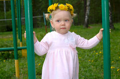 Pretty little girl with dandelion flower garland. Royalty Free Stock Photo