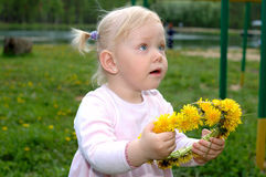 Pretty little girl with dandelion flower garland. Royalty Free Stock Photos