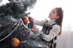 Pretty little girl decorate big christmas tree Stock Photo