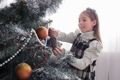 Pretty little girl decorate big christmas tree Royalty Free Stock Image