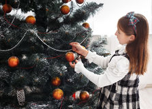 Pretty little girl decorate big christmas tree Royalty Free Stock Photos
