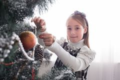 Pretty little girl decorate big christmas tree Royalty Free Stock Photography