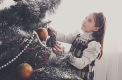 Pretty little girl decorate big christmas tree Stock Photography